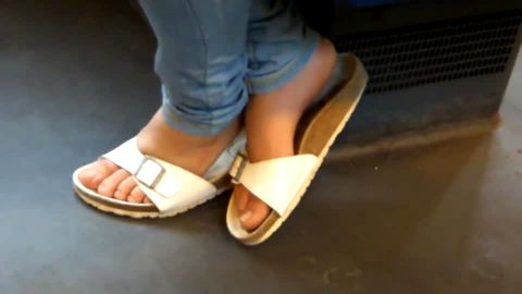 European beauty on train in white sandals
