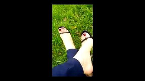 Sweet feet with red toenails in black flip flops