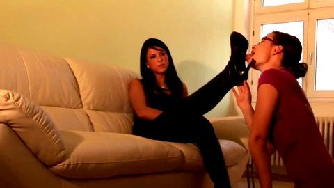 Cute female foot slave licking her domina's sexy black boots and socks on the sofa