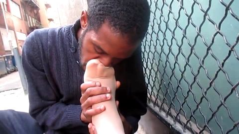 Black guy sniffs girl's feet in public