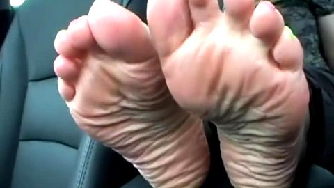 Older feet dangling from car