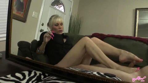 Mature blonde giving footjob while smoking