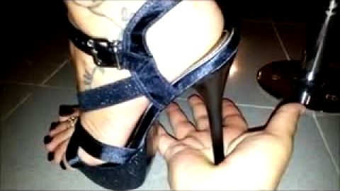 Crushing his hand with pointed stiletto heels