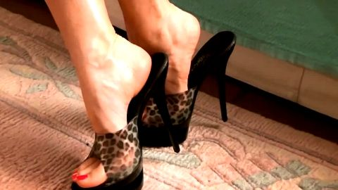 Leopard peeptoe mules on tan carpet