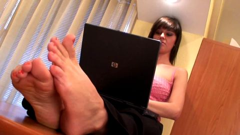Cute barefoot girl on computer