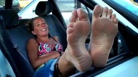 Hot Cougar shows dirty feet through van window