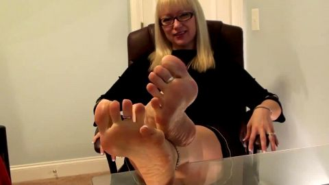 Pedicured mature blonde rests feet on glass table