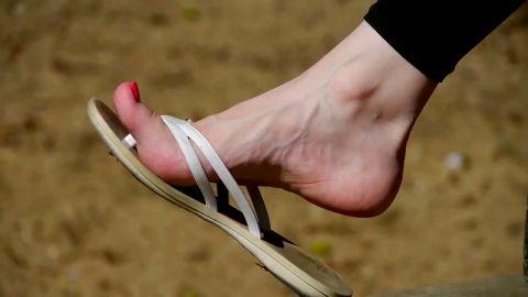 Flip-flops dangling off of painted toes