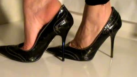 Amateur lifting feet out of pointed toe black leather heels
