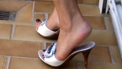 Leggy amateur pulls feet out of white mules