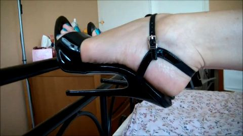 Open toed stilettos pressed against footboard