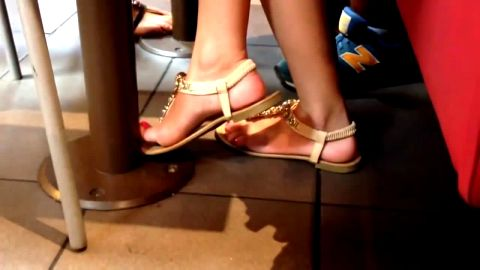 Beautifully Pedicured Feet In Sexy Golden Sandals Under The Table
