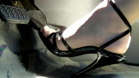 Feet in white stockings and sexy black Ankle Straps driving