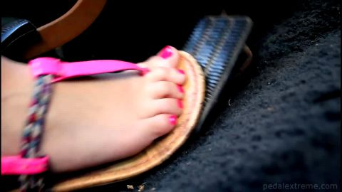 Sexy Foot With Pink Toenails and Sandals Pushes a Gas Pedal Down Rough