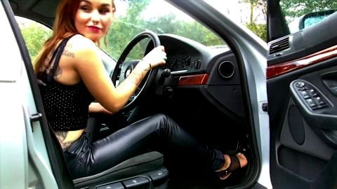 Tattoed hottie in leather pants revs and pedal pumps high performance car