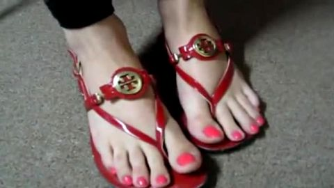 Red flip flops and matching toenails