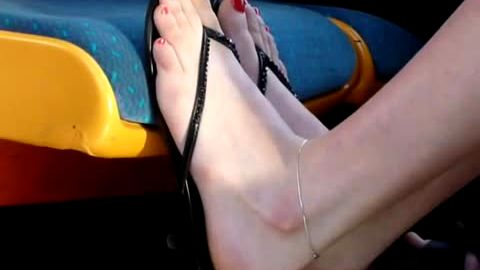 Pretty feet in sandals on bus
