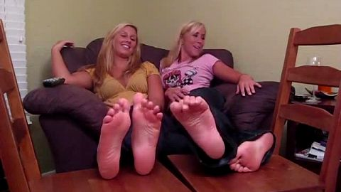 Two wonderful blonde chicks in jeans exposing their naked feet in front of camera