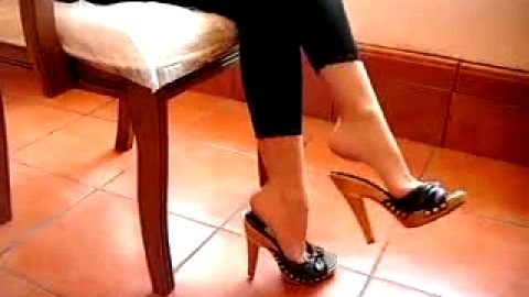 Horny girl sitting in the chair and playing with different types of shoes