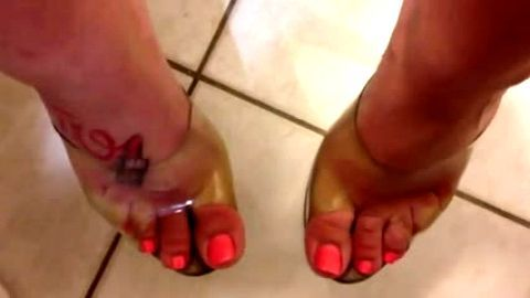 Tattoed feet in seethrough top sandals