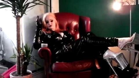 Blonde slut in naughty black latex outfit and high heels sitting on the couch and posing