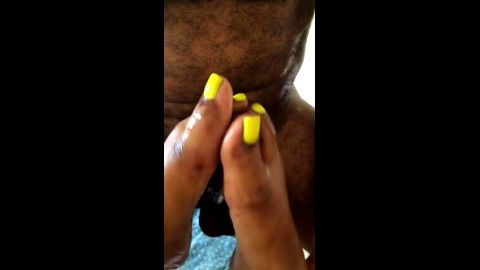 Sexy black feet with yellow nail polish stroking a massive cock until it cums