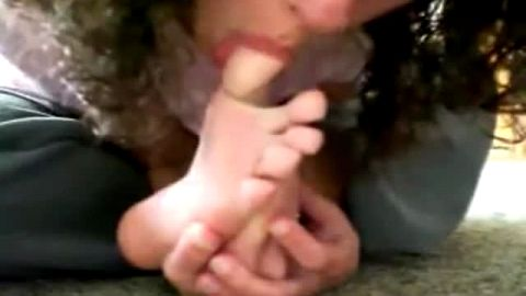 Cute girl with curly hair licks her amateur feet and sucks her toes on the floor