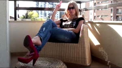 Blonde in tight jeans looks great wearing hot heels on her delicious feet at the balcony