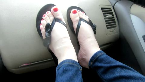 Amateur girl in tight jeans wearing flip flops on her feet in the car