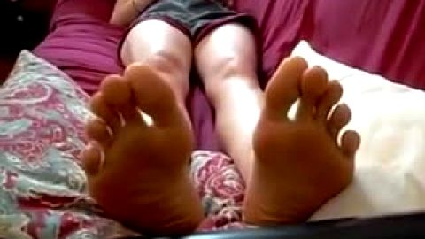 Skinny girl enjoys playing with her lovely feet in solo action