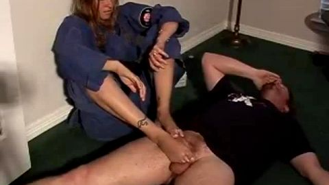 Pouty amateur in blue karate outfit giving footjob