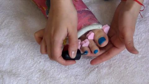 Babe with beautiful feet loves doing toe nail art in bed