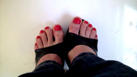 Girl in jeans has her sexy amateur feet with red nail polish on the camera