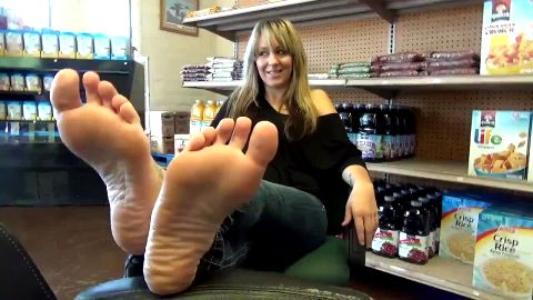 Blonde MILF in jeans does not mind showing her sexy naked feet at the store