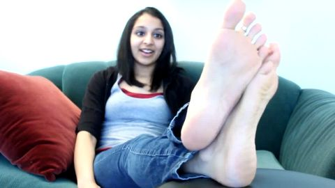 Cute teenage brunette enjoys sitting on the sofa with her sexy feet naked