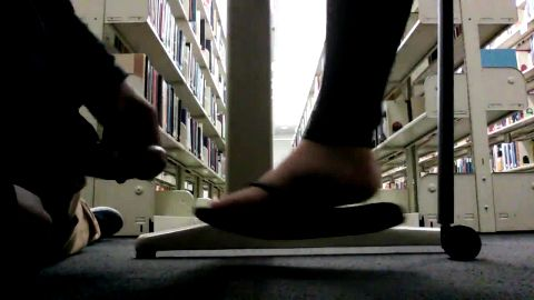 Creep cums on foot under table in library