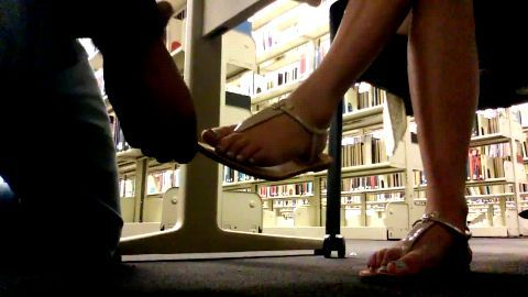 Cumming on her flip flops in library