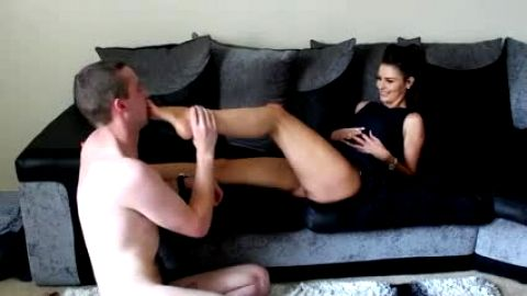 Naked male foot slave is obligated to lick his mistress's hot feet on the sofa