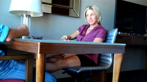 Blonde MILF gives a guy a perfect footjob with her mature feet at the office