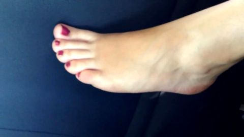 Hot amateur girl touching her attractive naked feet in the car