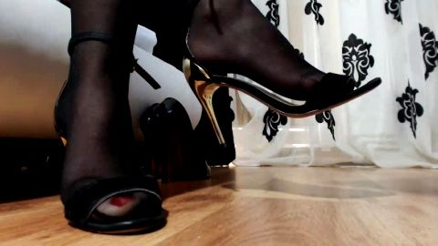 Girl in provocative black stockings dangling her black shoe while sitting