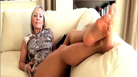 Provocative mature woman takes her shoes off and plays with her feet on the sofa