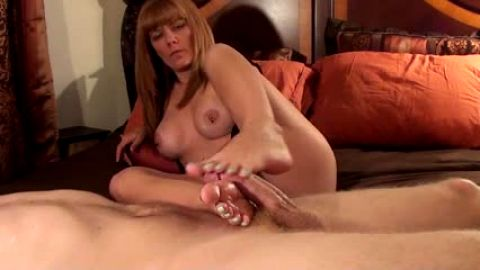 Mature tattoed woman gives slippery footjob