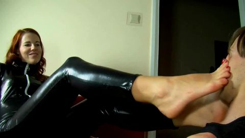 Redheaded mistress in black catsuit forcing feet upon slave