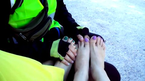 Two wild chicks give a nice footjob with their amateur feet in public