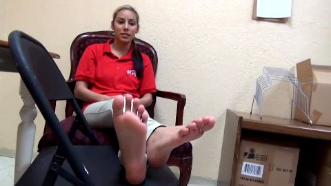 Beautiful girl sitting on the chair and exposing her lovely feet with red nail polish