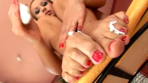 Candy rubs moisturizer into her feet and toes