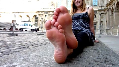 Sweet girl sitting on the street and showing her dirty amateur feet