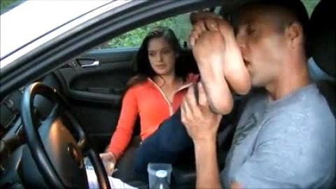 Kinky dude kissing and licking sexy girls's feet in the car