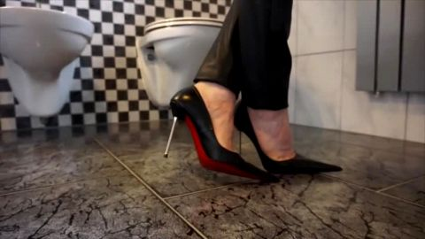 Woman looks sexy wearing ultra pointy stiletto and leather pants in the bathroom
